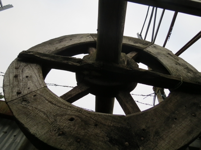Salvaged wooden six spoke pulley wheel complete with axle/shaft.